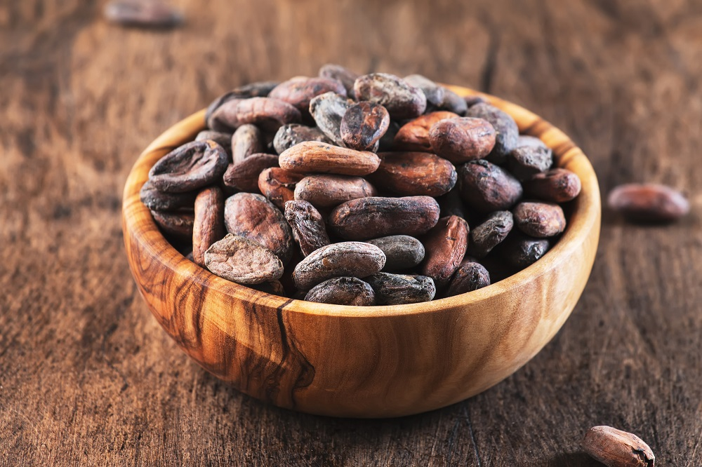 Unpeeled cocoa bean on wooden rustic background, close-up. Copy space